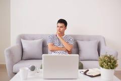 Νεαρός άνδρας που ανατρέχει εργαζόμενος στο lap-top στο σπίτι Στοκ Φωτογραφία