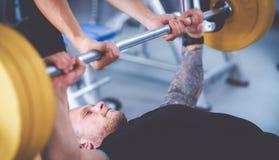 Νεαρός άνδρας που ανυψώνει το barbell στη γυμναστική με τον εκπαιδευτικό Στοκ φωτογραφία με δικαίωμα ελεύθερης χρήσης