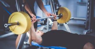 Νεαρός άνδρας που ανυψώνει το barbell στη γυμναστική με τον εκπαιδευτικό Στοκ Εικόνες