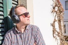 Νεαρός άνδρας που απολαμβάνει τη μουσική στις αστικές τοποθετήσεις Στοκ εικόνες με δικαίωμα ελεύθερης χρήσης