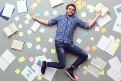 Νεαρός άνδρας που απομονώνεται στο γκρίζο υπόβαθρο με το χαμόγελο εγγράφων και σημειώσεων εύθυμο Στοκ εικόνες με δικαίωμα ελεύθερης χρήσης