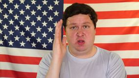Νεαρός άνδρας που αυξάνει το χέρι στο υπόβαθρο μιας ΑΜΕΡΙΚΑΝΙΚΗΣ σημαίας φιλμ μικρού μήκους