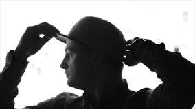Νεαρός άνδρας που βάζει σε ένα καπέλο του μπέιζμπολ απόθεμα βίντεο