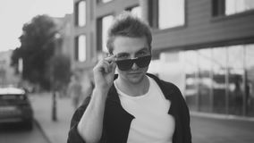 Νεαρός άνδρας που βγάζει τα γυαλιά ηλίου και που φαίνεται έκπληκτος απόθεμα βίντεο