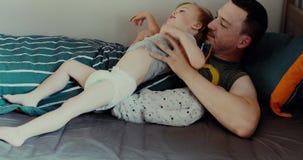 Νεαρός άνδρας που βρίσκεται στο κρεβάτι με τα παιδιά απόθεμα βίντεο