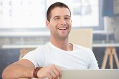 Νεαρός άνδρας που γελά ευτυχώς στο σπίτι στοκ εικόνες με δικαίωμα ελεύθερης χρήσης