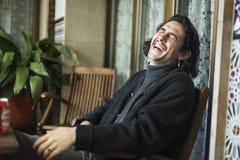 Νεαρός άνδρας που γελά σκληρά σε ένα πεζούλι στοκ φωτογραφία