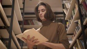Νεαρός άνδρας που γυρίζει τις σελίδες ενός βιβλίου στη βιβλιοθήκη μεταξύ των ραφιών απόθεμα βίντεο