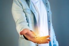 Νεαρός άνδρας που δίνει μια ιδέα λαμπτήρων βολβών σχετικά με ένα υπόβαθρο χρώματος Στοκ φωτογραφία με δικαίωμα ελεύθερης χρήσης