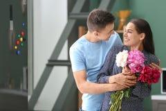 Νεαρός άνδρας που δίνει τα όμορφα λουλούδια στην αγαπημένη φίλη του στο εσωτερικό στοκ φωτογραφία