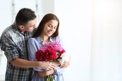 Νεαρός άνδρας που δίνει τα όμορφα λουλούδια στην αγαπημένη φίλη του στο εσωτερικό στοκ εικόνα