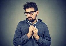Νεαρός άνδρας που δείχνει το αίσθημα ντροπαλός και ένοχος στην αδέξια κατάσταση στοκ εικόνα με δικαίωμα ελεύθερης χρήσης