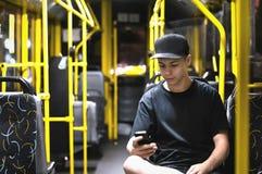 Νεαρός άνδρας που διαβάζει ένα μήνυμα σε δημόσιες συγκοινωνίες στοκ εικόνες