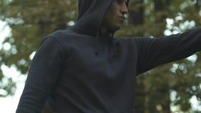 Νεαρός άνδρας που εκτελεί τα λακτίσματα, που ασκούν στις πολεμικές τέχνες υπαίθριες, τρόπος στην υγεία απόθεμα βίντεο