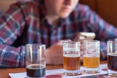 Νεαρός άνδρας που ελέγχει στις μπύρες app Στοκ εικόνες με δικαίωμα ελεύθερης χρήσης