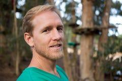 Νεαρός άνδρας που εξετάζει τη κάμερα και που στέκεται στο δάσος Στοκ φωτογραφία με δικαίωμα ελεύθερης χρήσης