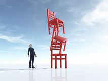 Νεαρός άνδρας που εξετάζει τρεις καρέκλες στην ισορροπία ελεύθερη απεικόνιση δικαιώματος