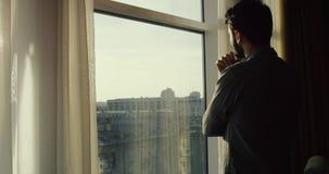 Νεαρός άνδρας που εξετάζει BT το παράθυρο την πόλη, σε αργή κίνηση 4K Πλησιάζει το παράθυρο, κατόπιν επιστρέφει και φεύγει απόθεμα βίντεο