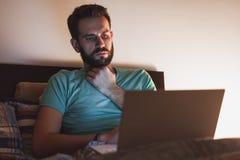 Νεαρός άνδρας που εργάζεται αργά στο κρεβάτι Στοκ Φωτογραφίες