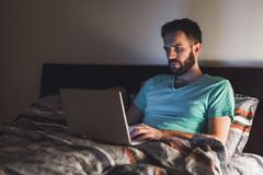 Νεαρός άνδρας που εργάζεται αργά στο κρεβάτι Στοκ Φωτογραφία