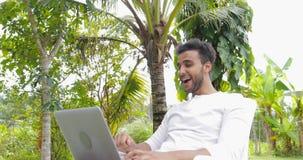 Νεαρός άνδρας που εργάζεται με το φορητό προσωπικό υπολογιστή υπαίθρια στο τροπικό ευτυχές χαμόγελο τύπων κήπων ισπανικό απόθεμα βίντεο