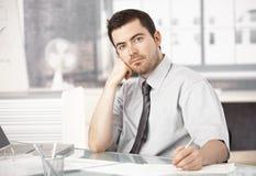 Νεαρός άνδρας που εργάζεται στη σκέψη σημειώσεων γραψίματος γραφείων στοκ φωτογραφία