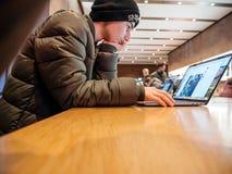 Νεαρός άνδρας που εργάζεται στη Apple MacBook υπέρ Στοκ φωτογραφία με δικαίωμα ελεύθερης χρήσης