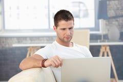 Νεαρός άνδρας που εργάζεται στο σπίτι στο lap-top Στοκ Εικόνες