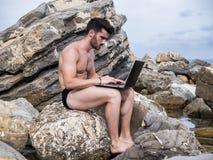 Νεαρός άνδρας που εργάζεται στο φορητό προσωπικό υπολογιστή στην παραλία στοκ φωτογραφίες με δικαίωμα ελεύθερης χρήσης