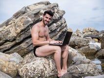Νεαρός άνδρας που εργάζεται στο φορητό προσωπικό υπολογιστή στην παραλία στοκ φωτογραφίες
