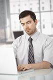 Νεαρός άνδρας που εργάζεται στο lap-top στο φωτεινό γραφείο Στοκ Φωτογραφία