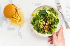 Νεαρός άνδρας που κάνει την επιλογή μεταξύ της υγιών σαλάτας και του γρήγορου φαγητού Στοκ φωτογραφίες με δικαίωμα ελεύθερης χρήσης
