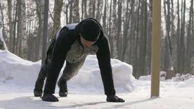 Νεαρός άνδρας που κάνει την ώθηση UPS και που τεντώνει τις ασκήσεις στη χειμερινή κατάρτιση υπαίθρια απόθεμα βίντεο