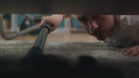 Νεαρός άνδρας που καθαρίζει ένα πάτωμα κάτω από ένα κρεβάτι που βρίσκεται στο πάτωμα που χρησιμοποιεί την ηλεκτρική σκούπα απόθεμα βίντεο