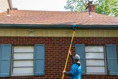 Νεαρός άνδρας που καθαρίζει soffit ενός ενός σπιτιού ιστορίας με μια βούρτσα σε έναν μακρύ πόλο Το σπίτι έχει τα μπλε παραθυρόφυλ στοκ φωτογραφία με δικαίωμα ελεύθερης χρήσης