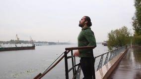 Νεαρός άνδρας που και που χρησιμοποιεί το smartphone στο πάρκο πόλεων Νέος ισχυρός όμορφος δρομέας στην πράσινη ένδυση, που έξω μ φιλμ μικρού μήκους