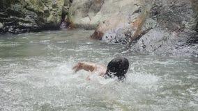 Νεαρός άνδρας που κολυμπά στον καταρράκτη στην τροπική ζούγκλα κίνηση αργή 1920x1080, hd απόθεμα βίντεο
