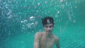 Νεαρός άνδρας που κολυμπά τα υποβρύχια waterdrops που εμπίπτουν και που καταβρέχουν στον καταπληκτικό μπλε ωκεανό κίνηση αργή 120 απόθεμα βίντεο