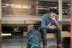 Νεαρός άνδρας που κρατά το έξυπνο τηλέφωνο και που χρησιμοποιεί το playlist μουσικής με την αναμονή Στοκ φωτογραφία με δικαίωμα ελεύθερης χρήσης