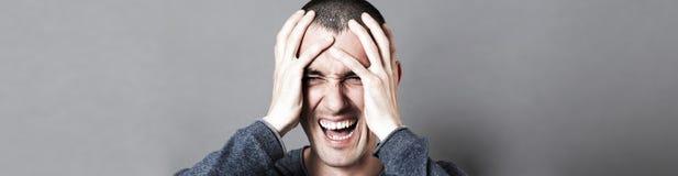 0 νεαρός άνδρας που κρατά το κεφάλι του, που κραυγάζει την ουδετεροποίησή του, έμβλημα Στοκ φωτογραφίες με δικαίωμα ελεύθερης χρήσης