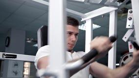 Νεαρός άνδρας που λυγίζει τους θωρακικούς μυς του στον προσομοιωτή Υγεία, αθλητισμός απόθεμα βίντεο