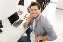 Νεαρός άνδρας που μιλά στο κινητό τηλέφωνο εργαζόμενος στην αρχή Στοκ Εικόνα