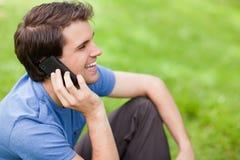 Νεαρός άνδρας που μιλά στο τηλέφωνο καθμένος στη χλόη Στοκ εικόνες με δικαίωμα ελεύθερης χρήσης