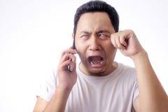 Νεαρός άνδρας που μιλά στο τηλέφωνο, συγκλονισμένη ανησυχημένη έκφραση στοκ εικόνες