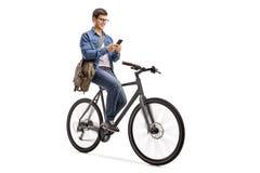 Νεαρός άνδρας που οδηγά ένα ποδήλατο και που χρησιμοποιεί ένα τηλέφωνο Στοκ φωτογραφία με δικαίωμα ελεύθερης χρήσης