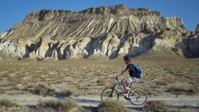 Νεαρός άνδρας που οδηγά ένα ποδήλατο σε ένα υπόβαθρο ενός τοπίου με τα βουνά απόθεμα βίντεο