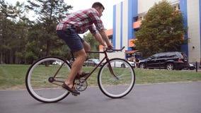 Νεαρός άνδρας που οδηγά το εκλεκτής ποιότητας ποδήλατο στο δρόμο πόλεων Φίλαθλη ανακύκλωση τύπων στο αστικό περιβάλλον Υγιής ενερ απόθεμα βίντεο