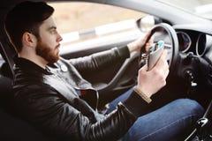 Νεαρός άνδρας που οδηγεί ένα αυτοκίνητο με μια φιάλη σιδήρου Στοκ Εικόνα
