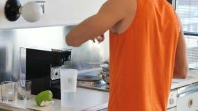 Νεαρός άνδρας που πίνει ένα ποτό καταφερτζήδων ή ένα πρωτεϊνικό κούνημα απόθεμα βίντεο