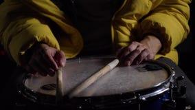 Νεαρός άνδρας που παίζει ένα τύμπανο που τίθεται σε ένα σκοτεινό δωμάτιο 4K Clous επάνω Κινηματογράφηση σε πρώτο πλάνο των χεριών απόθεμα βίντεο